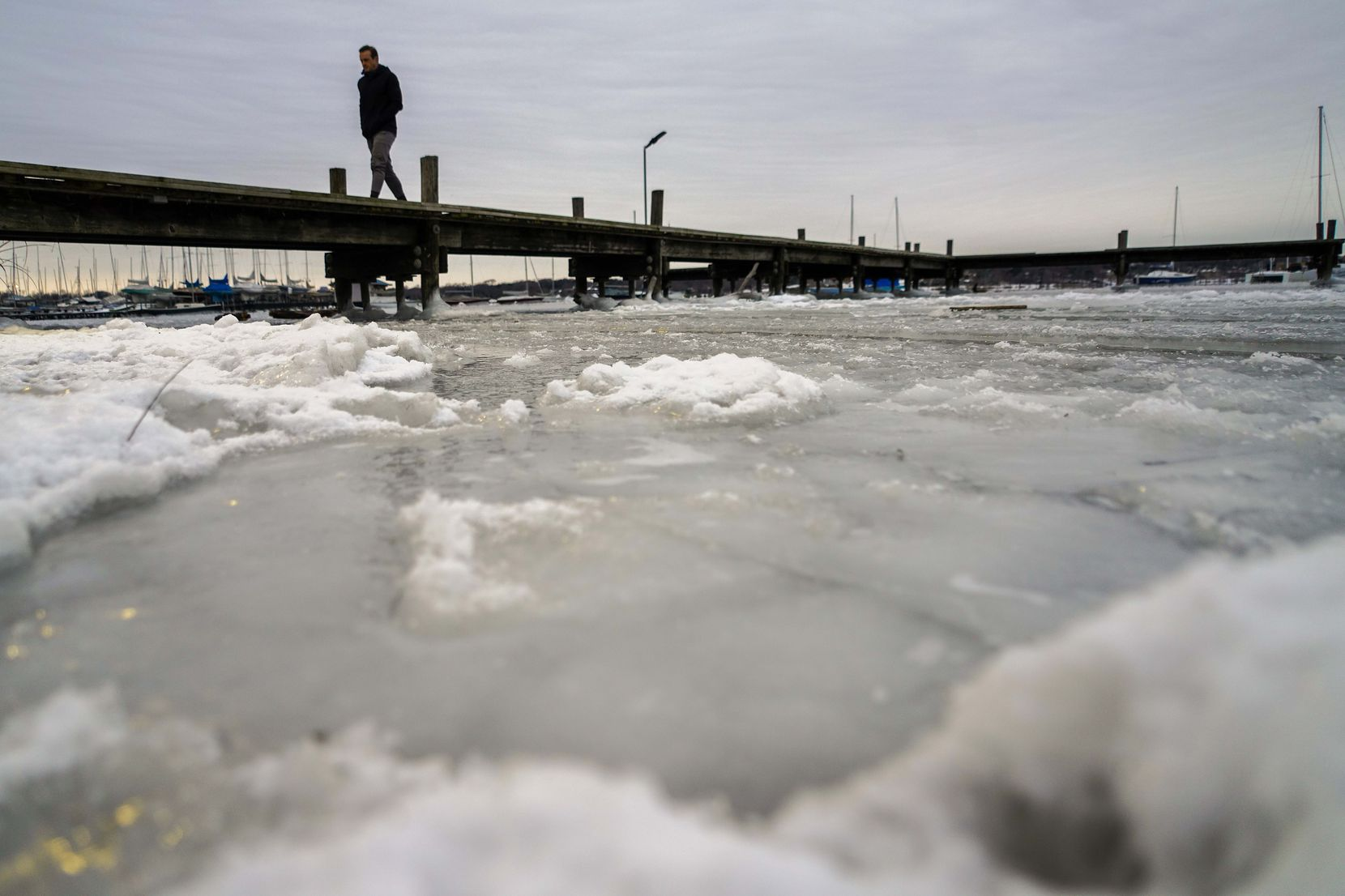 Frozen waters of White Rock Lake surround a pier after a winter storm brought snow and freezing temperatures to North Texas on Tuesday, Feb. 16, 2021, in Dallas. Another winter storm could dump 5 more inches of snow on Dallas-Fort Worth. (Smiley N. Pool/The Dallas Morning News)