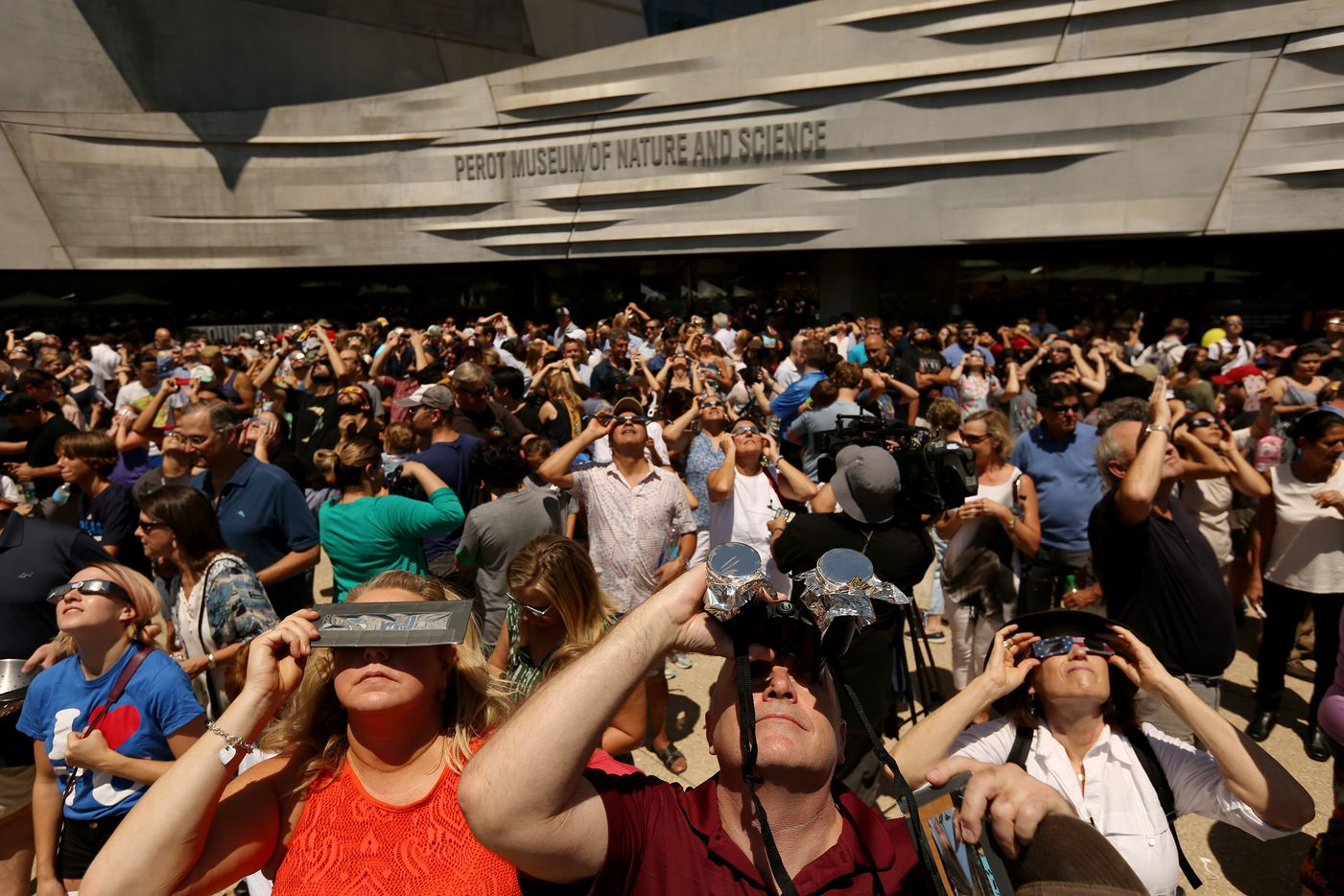 People watch the sun during a solar eclipse outdoor watch party at the Perot Museum of Nature and Science.