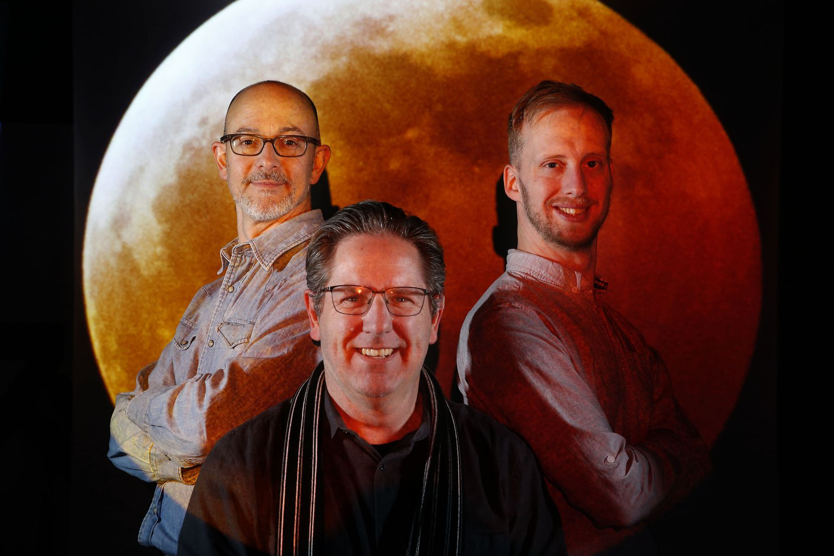 Michael Hamtil, (from left) Daniel Carde and Tom Fox in The Dallas Morning News photo studio for a story about shooting the Super Blood Wolf Moon, on Jan. 23, 2019. Carde's photo of the total lunar eclipse which took place Sunday, January 20, 2019 is projected in the background.