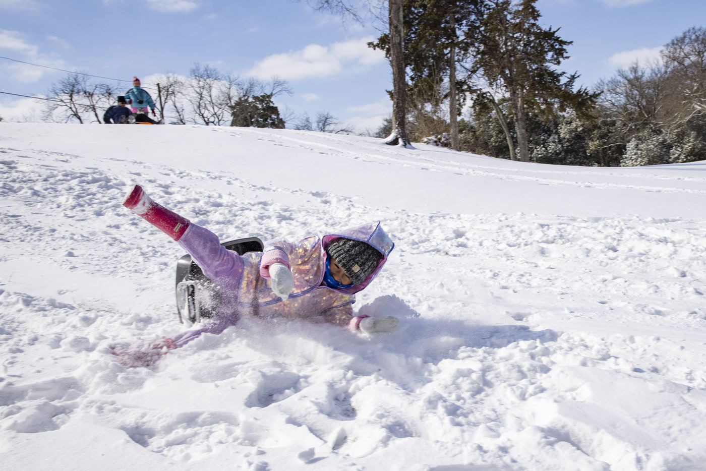 Mia Donjuan, 4, wipes off of her pan as she slides down a hill in the Dallas Elmwood neighborhood on Monday, Feb. 15, 2021. (Juan Figueroa/ The Dallas Morning News)