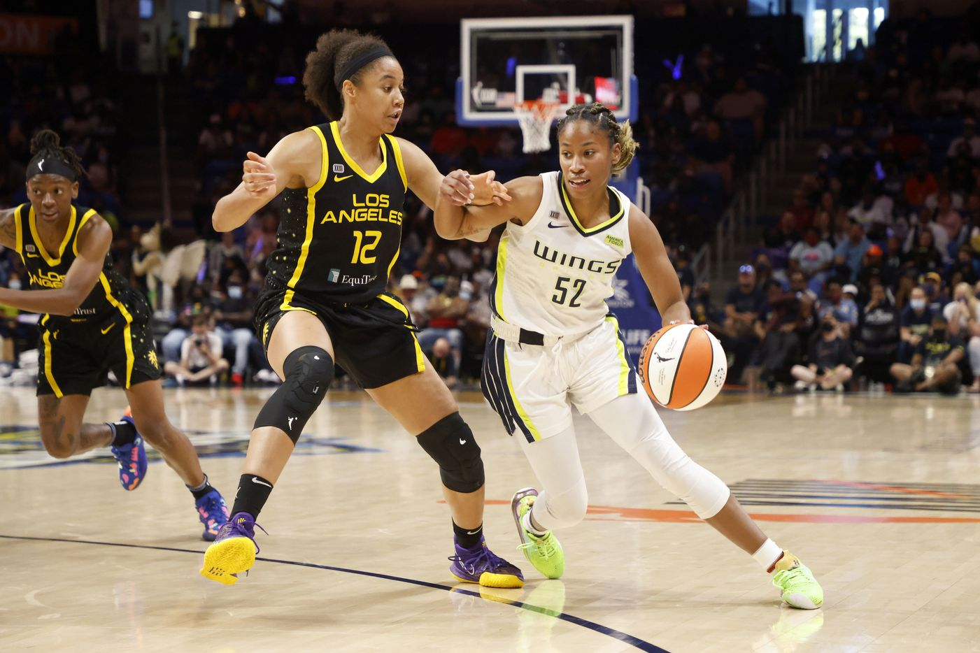 Dallas Wings guard Tyasha Harris (52) drives past Los Angeles Sparks forward Nia Coffey (12) during the second half of a WNBA basketball game in Arlington, Texas on Sunday, Sept. 19, 2021. (Michael Ainsworth/Special Contributor)