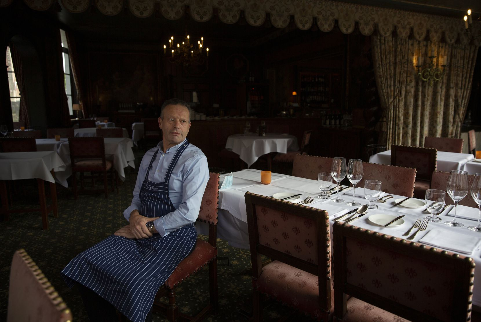 Restaurant co-owner Luc Broes sits inside his empty dining room at the Duc de Bourgogne restaurant in Bruges, Belgium.