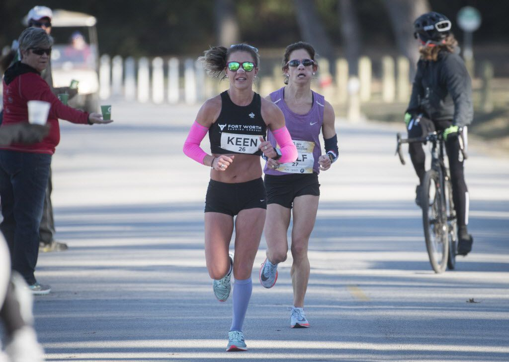 Caitlin Keen, front, and Chandler Self approach the 15.5 mile along White Rock Lake during the BMW Dallas Marathon. Self finished first among females with a time of 2:53:58.  (Rex C. Curry/Special Contributor)