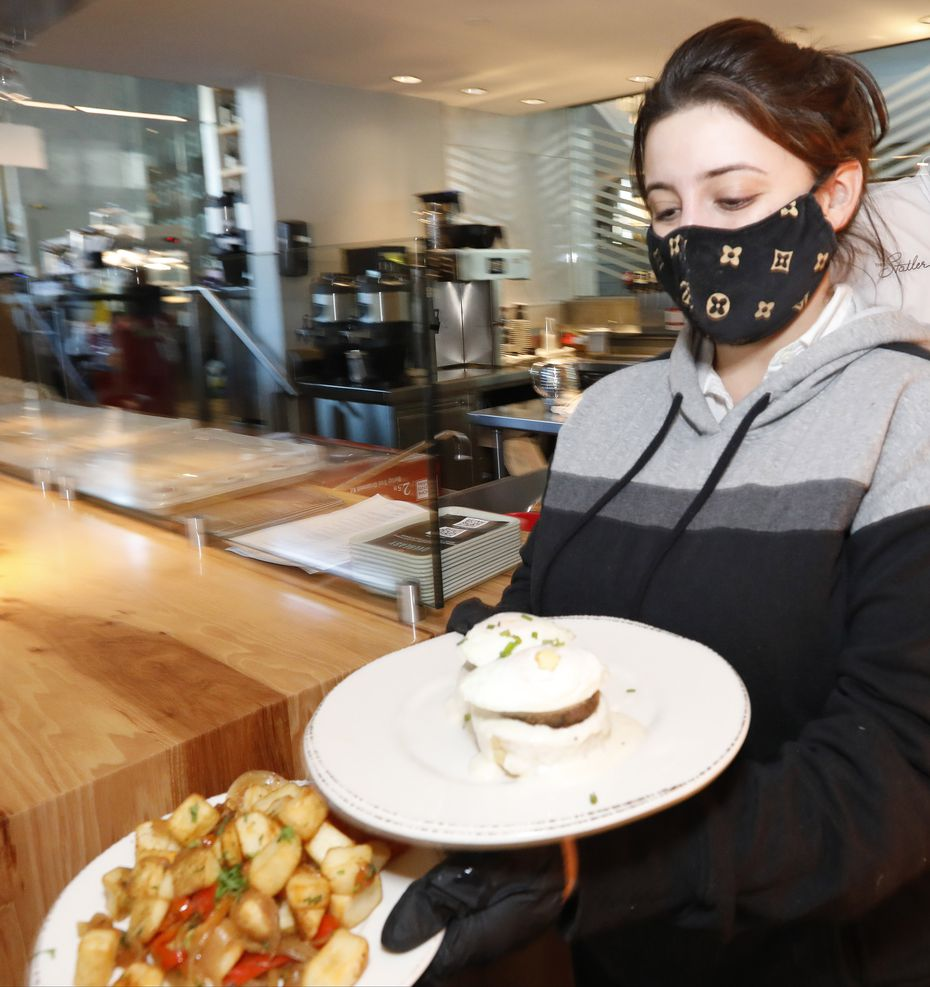 Server Kaitlyn Gonzales takes food to a customer's table at Overeasy in Dallas. The shop sold coffee all week — mostly drip coffee instead of the popular lattes — and hot breakfast.
