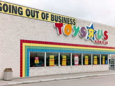 A Going Out Of Business sign hangs over a Toys R Us. Burdened with debt from a leveraged buyout, the toy chain filed for bankruptcy almost three years ago and closed its stores the following year.