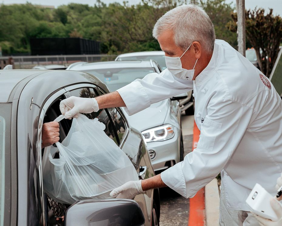 Executive chef and Fort Worth restaurant owner Jon Bonnell hands food to a driver during the coronavirus pandemic.