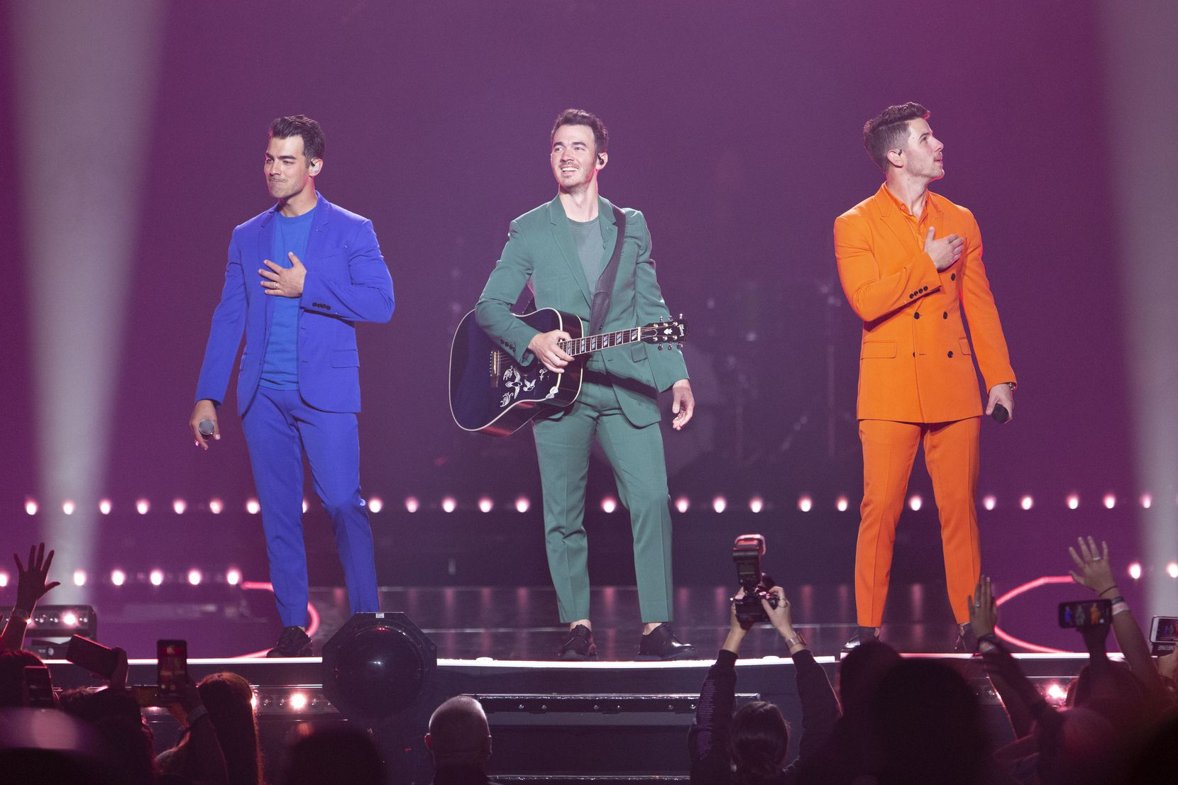Jonas Brothers members Joe Jonas, left, Kevin Jonas, middle, and Nick Jonas, right, acknowledge the crowd after the opening song at American Airlines Center in Dallas, Texas on Sept. 25, 2019.