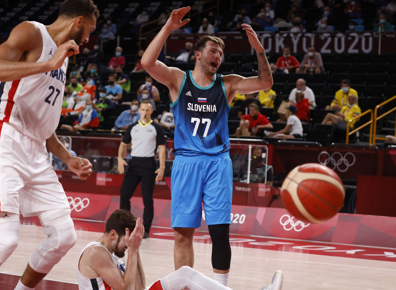 Slovenia's Luka Doncic (77) reacts after getting called for a foul on France's Nando de Cold (12) as France's Rudy Gobert (27) looks on during the second half of a men's basketball semifinal at the postponed 2020 Tokyo Olympics at Saitama Super Arena, on Thursday, August 5, 2021, in Saitama, Japan. France defeated Slovenia 90-89. Slovenia will play in the bronze medal game. (Vernon Bryant/The Dallas Morning News)