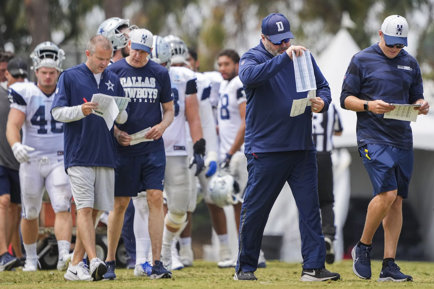Dallas Cowboys head coach Mike McCarthy (center) walks between drills with offensive coordinator Kellen Moore (right) during a practice at training camp on Wednesday, Aug. 11, 2021, in Oxnard, Calif.