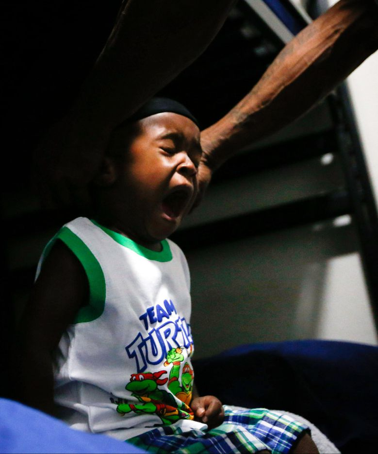 Jordan Miller, 2, yawns while his dad finishes getting him ready for the day at The Family Place men's shelter in Dallas. Jordan and his dad, Joshua Miller, start their day at 4 a.m. so they are ready for the day care van's early morning arrival. (Tailyr Irvine/The Dallas Morning News)