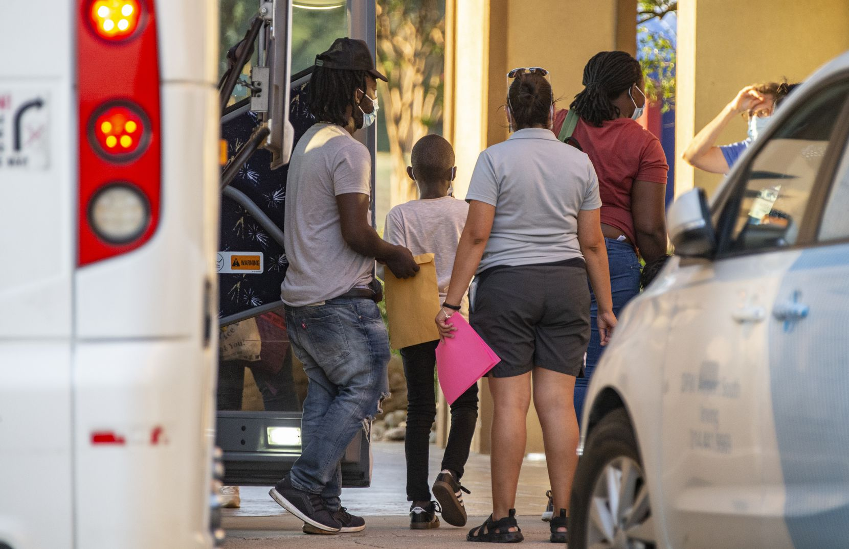 Volunteers with Faith Forward Dallas helped migrant families from Haiti and Cuba exit a bus at a hotel in Irving on Wednesday. The bus arrived from the border city of Del Rio, Texas.