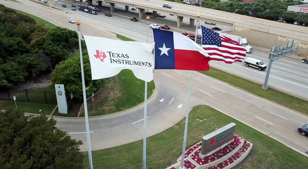 Flags fly at the Texas Instruments campus in Dallas. The company said Thursday that it will build a semiconductor facility in Richardson that will create nearly 500 jobs.