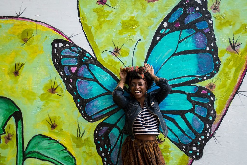Essence Mahara poses for a photo against a backdrop of paintings of flora and fauna at Bishop and Melba streets in the Bishop Arts District on Tuesday, April 18, 2017, in Dallas. The installation of public art in the neighborhood, a temporary wall of the murals, forms a small park-like plaza and hides forthcoming construction in the neighborhood. (Smiley N. Pool/The Dallas Morning News)