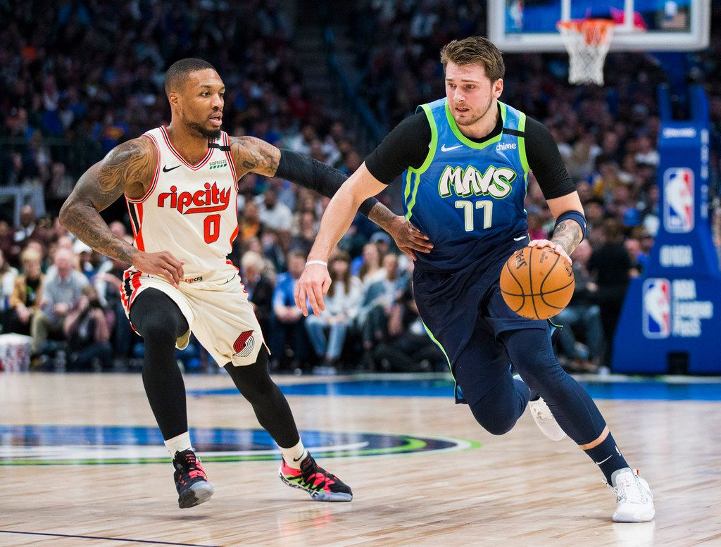 The Dallas Mavericks' Luka Doncic (77) drives against the Portland Trail Blazers' Damian Lillard (0) during the first quarter on Friday, Jan. 17, 2020, at American Airlines Center in Dallas.