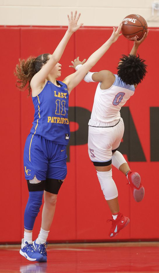 Skyline senior Zyniah Thomas (0) attempts a shot as Lakeview Centennial senior Alexis Gie (11) defends during a girls basketball first-round playoff game at Hillcrest High School in Dallas, Saturday, February 13, 2021. Skyline won 49-42. (Brandon Wade/Special Contributor)