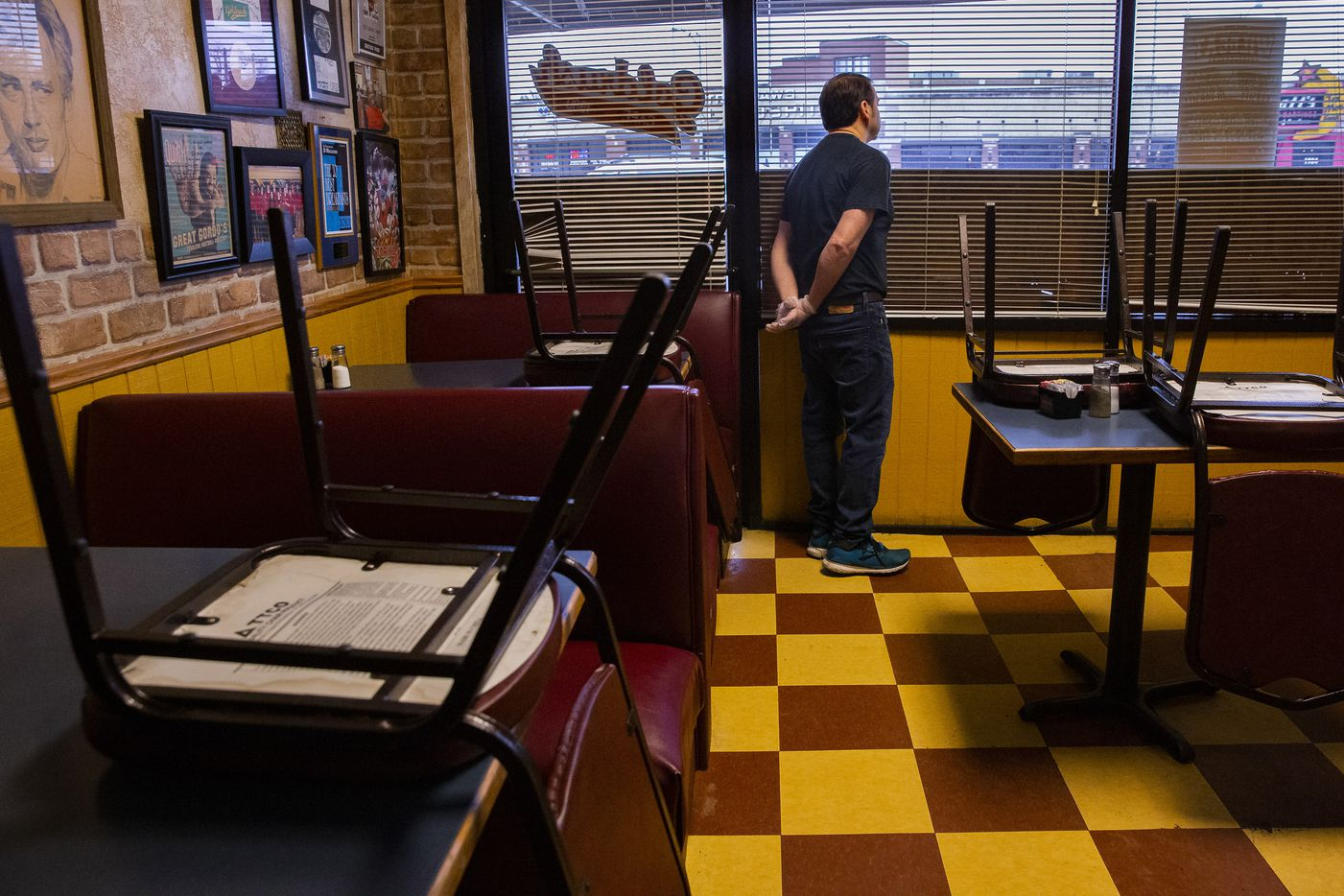 Goldrush Cafe Owner George Sanchez looks outside his window as he waits for customers on March 16, 2020 in Dallas. The outbreak of the new coronavirus has led Sanchez to limit the number of people allowed in the restaurant and to primarily do to-go orders.