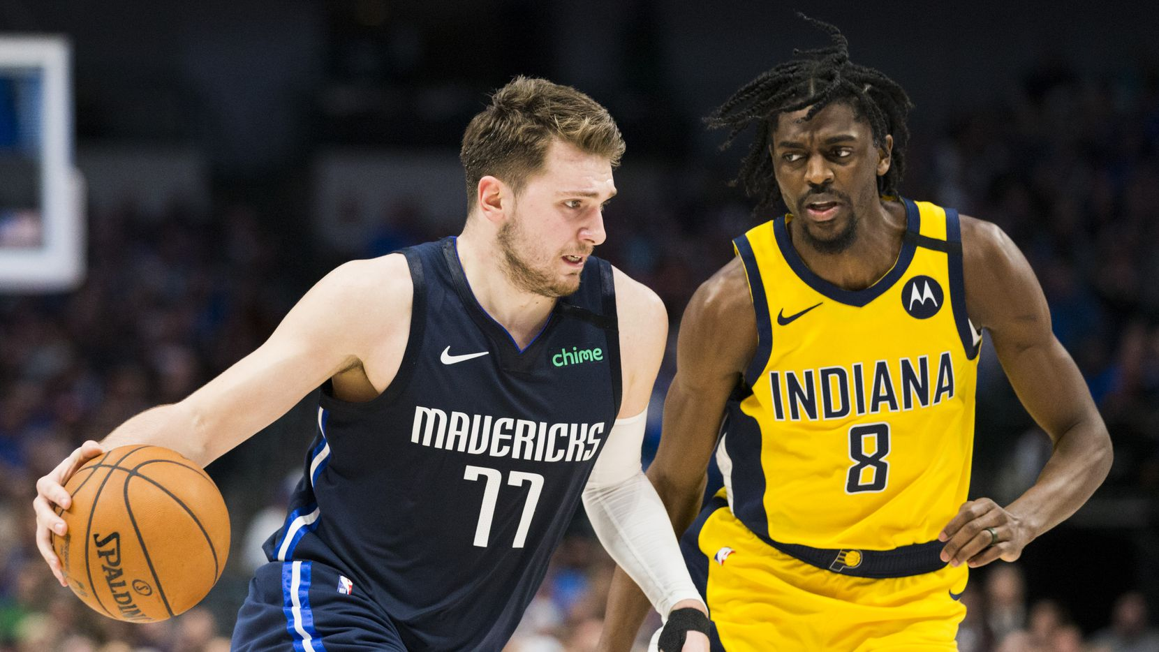 FILE - Mavericks guard Luka Doncic (77) pushes the ball down the court while defended by Pacers forward Justin Holiday (8) during the third quarter of a game on Sunday, March 8, 2020, at American Airlines Center in Dallas.