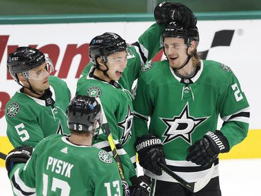 Dallas Stars left wing Jason Robertson (21) congratulates left wing Roope Hintz (right) on his third period goal against the Chicago Blackhawks at the American Airlines Center in Dallas, Tuesday, March 9, 2021. The Stars defeated the Blackhawks, 6-1. (Tom Fox/The Dallas Morning News)