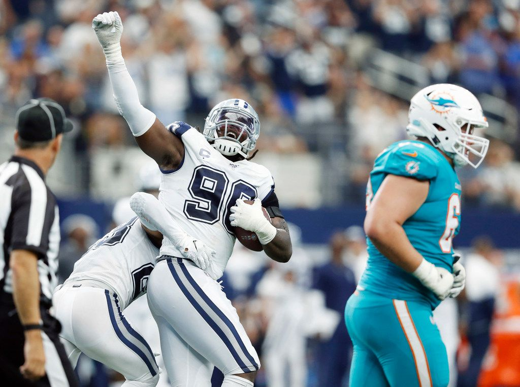 Dallas Cowboys defensive end Demarcus Lawrence (90) celebrates with Dallas Cowboys defensive back Darian Thompson (23) after gaining possession of the ball off a fumble from Miami Dolphins running back Kenyan Drake (32) during the first half of play at AT&T Stadium in Arlington, Texas on Sunday, September 22, 2019.