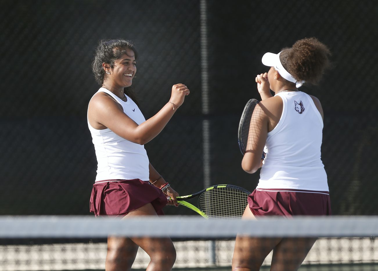 Saundarya Vedula (let) high fives teammate Tamiya Lintz after they scored a point in the 5A girls doubles match at the UIL State Tennis finals at Northside Tennis on Friday, May 21, 2021.