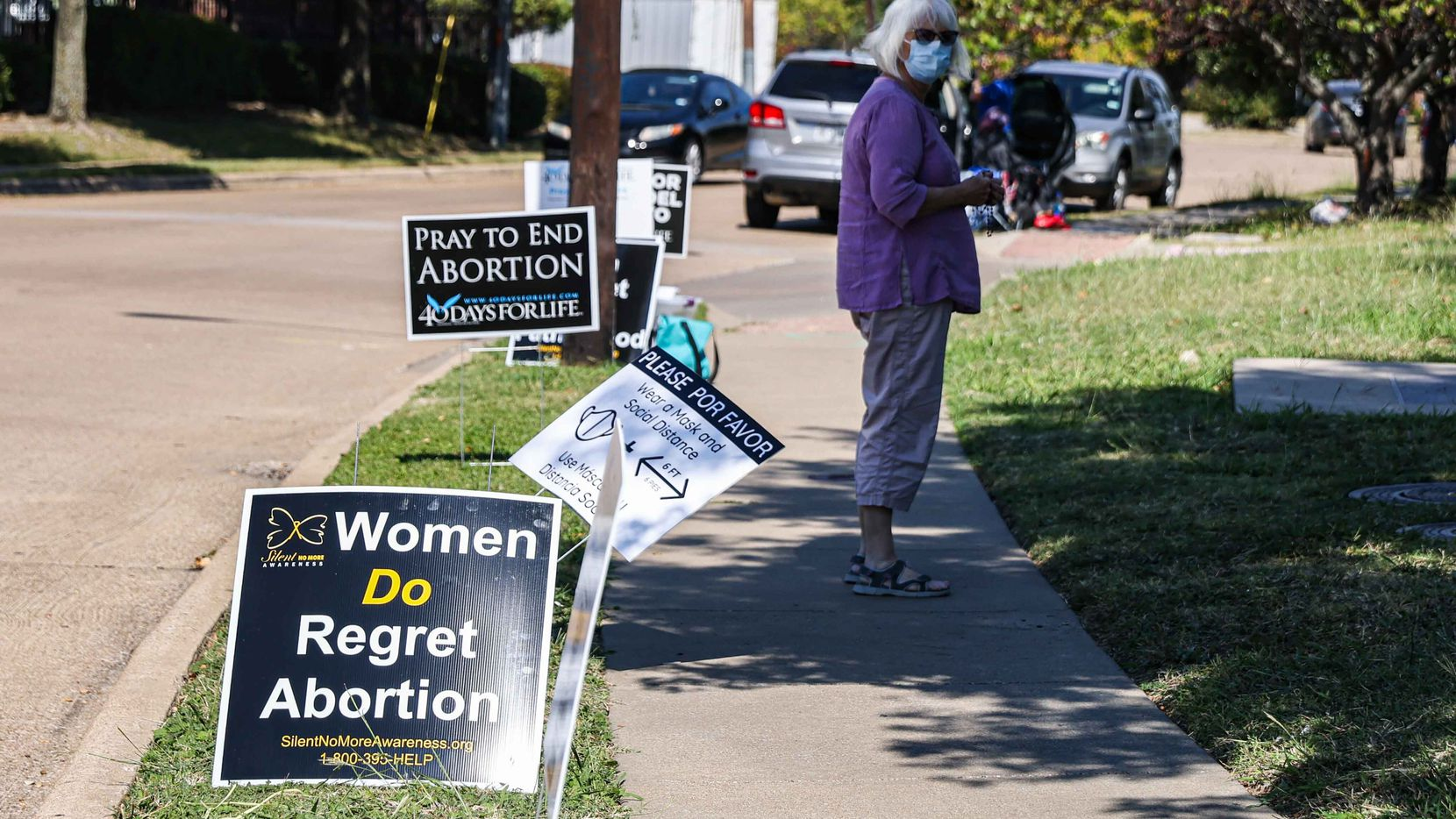 A protester stands on the sidewalk near Planned Parenthood next to anti-abortion signs in Dallas on Thursday.