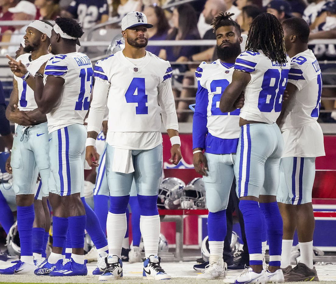 Dallas Cowboys quarterback Dak Prescott (4) watches from the sidelines with wide receiver Cedrick Wilson (1), wide receiver Michael Gallup (13), running back Ezekiel Elliott (21) wide receiver CeeDee Lamb (88) and wide receiver Amari Cooper (19) during the second quarter of an NFL football game against the Arizona Cardinals at State Farm Stadium on Friday, Aug. 13, 2021, in Glendale, Ariz.