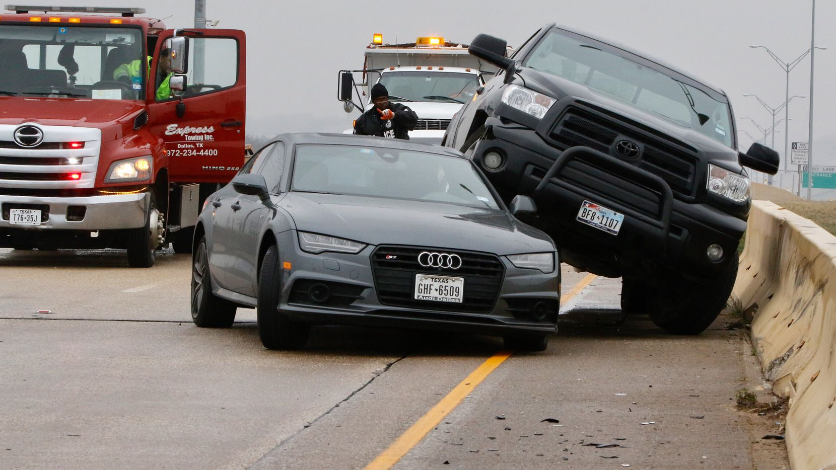 Richard Garay (left) of Express Towing talks to Dallas police Officer J.W. Jacobs after he arrived at the scene of a wreck on the southbound lanes U.S. Highway 67 over Camp Wisdom Road in Dallas on Thursday. Freezing temperature and wet conditions overnight led to icy roads, causing dozens of accidents.