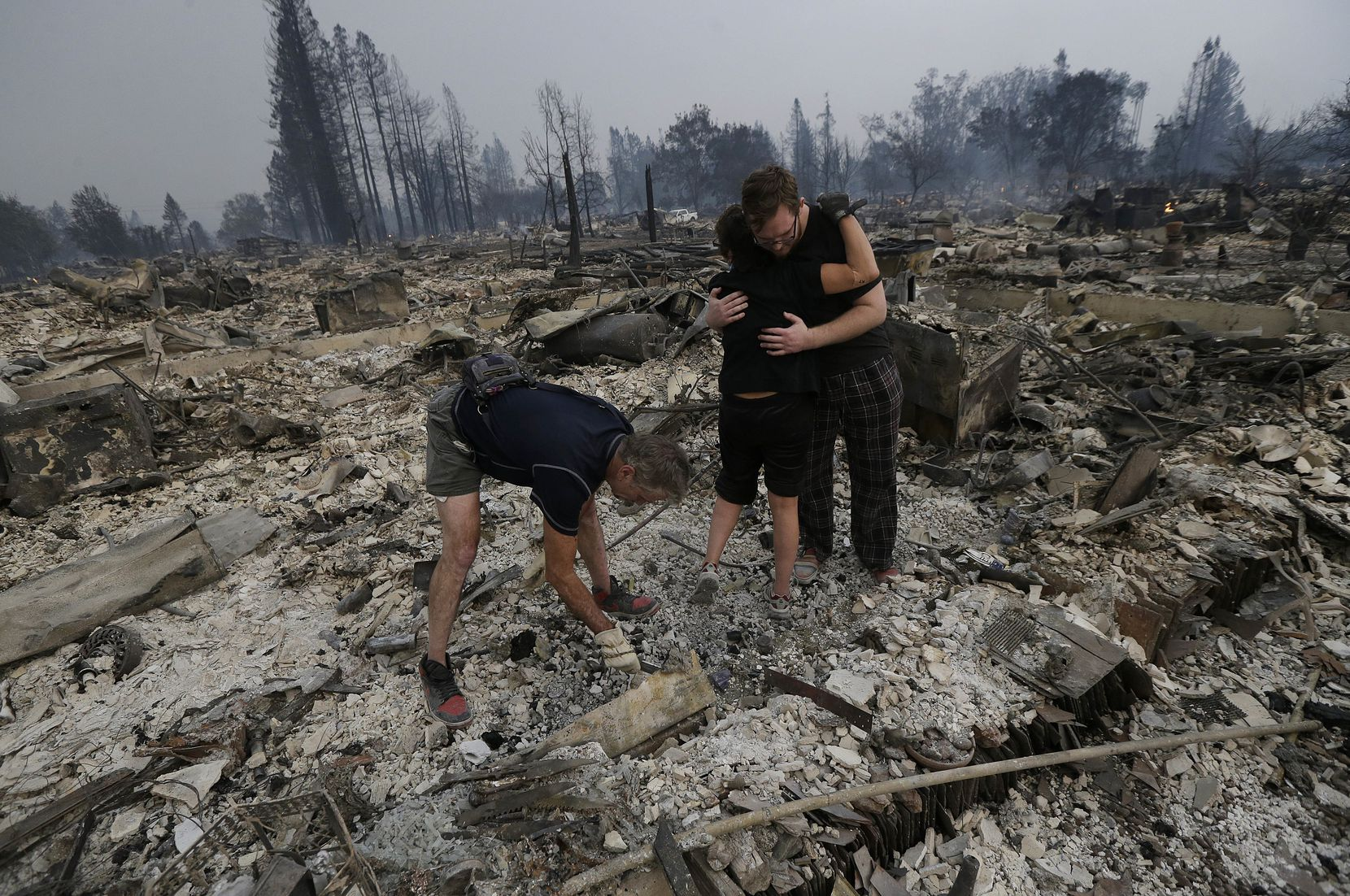 Michael Pond, left, looks through ashes as his wife Kristine, center, gets a hug from Zack Thurston, their daughter's boyfriend, while they search the remains of their home destroyed by fires in Santa Rosa, Calif., Monday, Oct. 9, 2017.