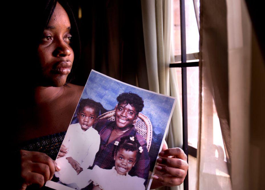 Shennel Gardner held a portrait of her brother, Devon Green (left); her mother, Debra Gardner (center); and herself in 2011. Shennel and Devon were present when their mother, Debra, was fatally shot by Duane Buck in 1995.