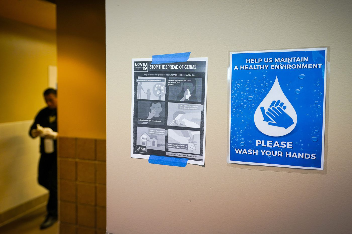 Signs advocate hand washing and CDC guidelines for stopping the spread of the new coronavirus as a worker cleans a restroom during the NCWA national championships at the Allen Events Center on Friday, March 13, 2020, in Allen, Texas.