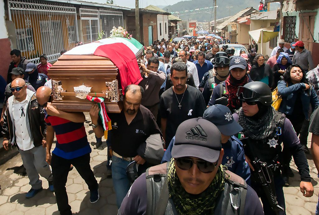 Police guard as relatives and friends of Nahuatzen Mayor, David Otilica, carry his coffin during his funeral in Nahuatzen, Michoacan State, Mexico on April 25, 2019. Otilica was kidnapped and murdered.