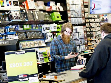 Employee Matt Doyle looks over games being traded in by a customer at a GameStop store in Illinois.