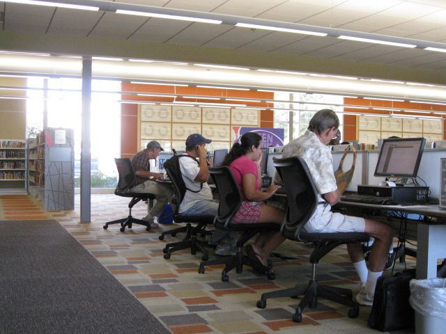 Patrons access computers at the Dallas Public Library. AT&T and the Public Library Association have developed digital literacy courses to help caregivers better support students with online learning.