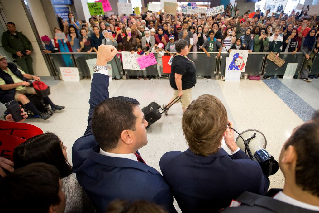 Attorney Chris Hamilton (with megaphone) addresses protestors at DFW International Airport opposed to President Donald Trump's executive order barring certain travelers on Sunday, Jan. 29, 2017.  (Smiley N. Pool/The Dallas Morning News)