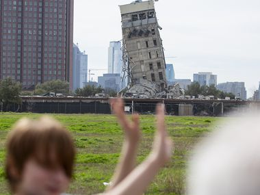 Randy Gibson takes a photo of his son Andrew, 11, in front of the 'Leaning Tower of Dallas' on Feb. 17, 2020 in Dallas. A demolition of the former Affiliated Computer Services tower on Sunday morning left the central core behind.