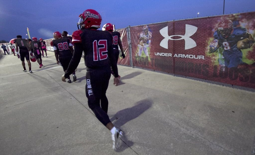 Cedar Hill quarterback Avery Davis (12), as well as other members of the Longhorns football team walk from the team dressing room past a large sign sporting Longhorns players with the Under Armour logo.  The two teams played their class 6A football game at Longhorn Stadium in Cedar Hill on October 9, 2015. (Steve Hamm/Special Contributor)