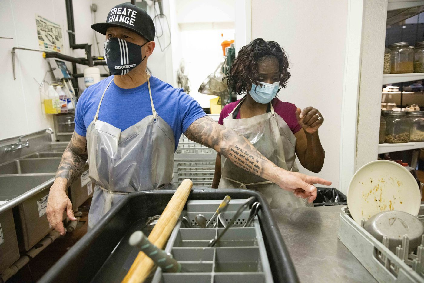 Dallas Police Chief Eddie García (left) along with officer Pearl Mcdowell (right) ask Payton Ceasar, 17, if they can wash the tray of dirty dishes during their shift as volunteer dishwashers at Café Momentum, which employs formerly youth coming out of juvenile detention, on Friday, May 14, 2021, in Dallas. (Juan Figueroa/The Dallas Morning News)
