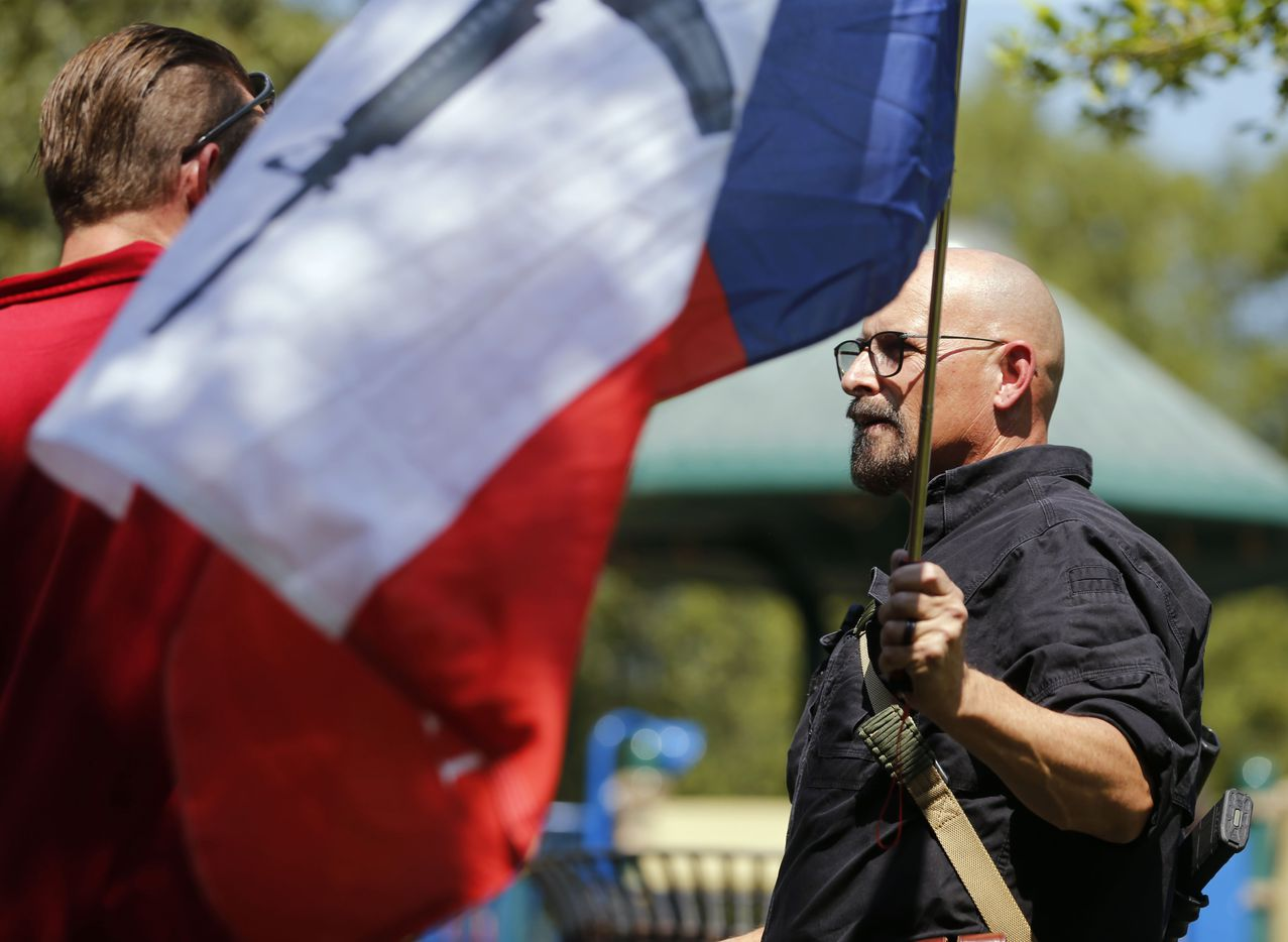 Matthew Blevins (left) and John Swicegood (right) who was wearing an AR-15, discuss their differences of opinion during a campaign event for Democratic Presidential candidate Beto O'Rourke at Haggard Park in Plano, Texas, on Sunday, September 15, 2019.