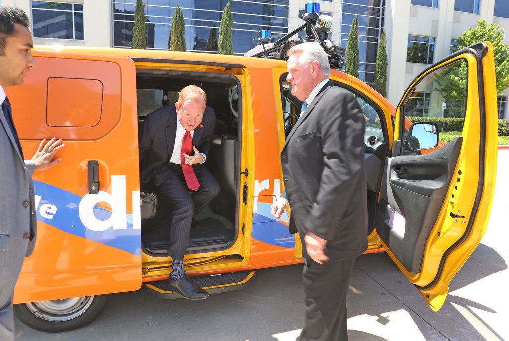 Frisco Mayor Jeff Cheney is greeted by DCTA's Carter Wilson as he emerges from the back seat of a self-driving car after a press conference and demonstration of self-driving cars in Frisco's North Platinum Corridor on May 7, 2018. The city is looking for transportation solutions as it experiences a population boom.