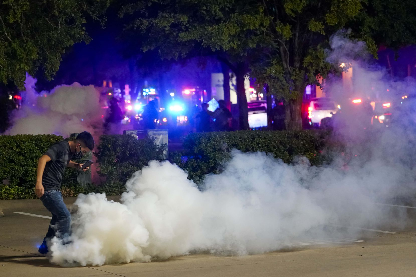 A protester tries to kick away a canister of teargas after it landed at his feat as Dallas police attempt to disperse protesters at the corner of Lamar and Young Streets as they march against police brutality on Friday, May 29, 2020, in Dallas.
