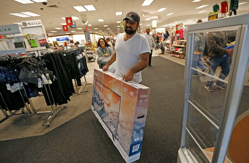 Shopper Ramon Phillips (right) carries a 55-inch TV after shopping with his sister Subhadra Phillips at the Kohl's store at Medallion Center in Dallas, Thursday, Nov. 23, 2017.