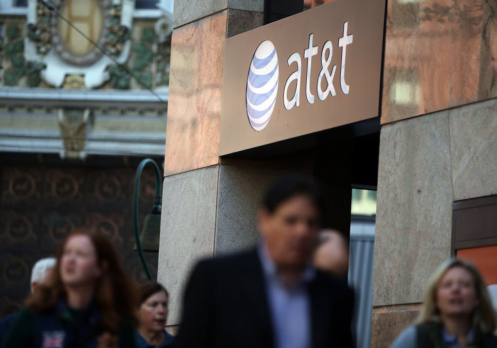 Pedestrians walk by an AT&T store on October 23, 2013 in San Francisco, California.