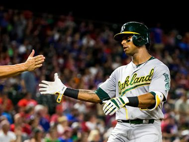 Oakland Athletics left fielder Khris Davis gets a hand from third baseman Danny Valencia after hitting a home run during the third inning against the Texas Rangers at Globe Life Park on Friday, Sept. 16, 2016, in Arlington.