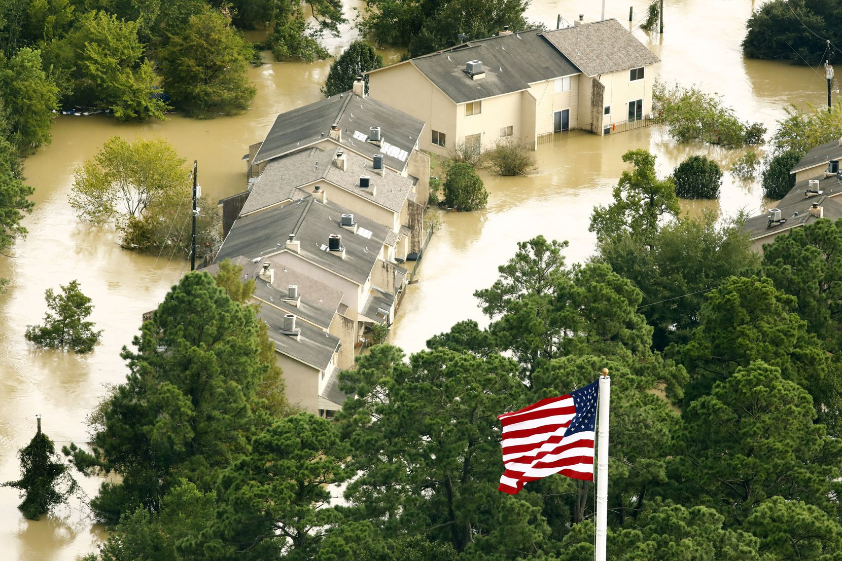 The U.S. flag flies before flooded condo buildings sitting in the the overflowing San Jacinto River in Humble, Texas, Wednesday, August 30, 2017. Hurricane Harvey inundated the Houston area with several feet of rain.