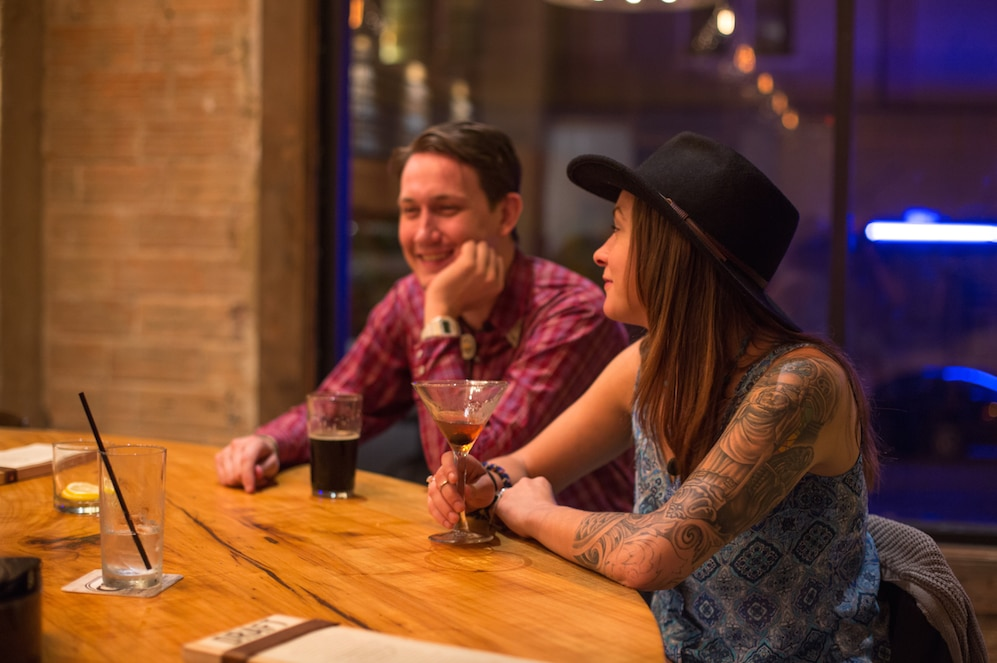 Dentonites Nathan West and Abby Chapman enjoy drinks at the bar during Barley and Board's soft opening event on Tuesday, August 11, 2015 in Denton, Texas.