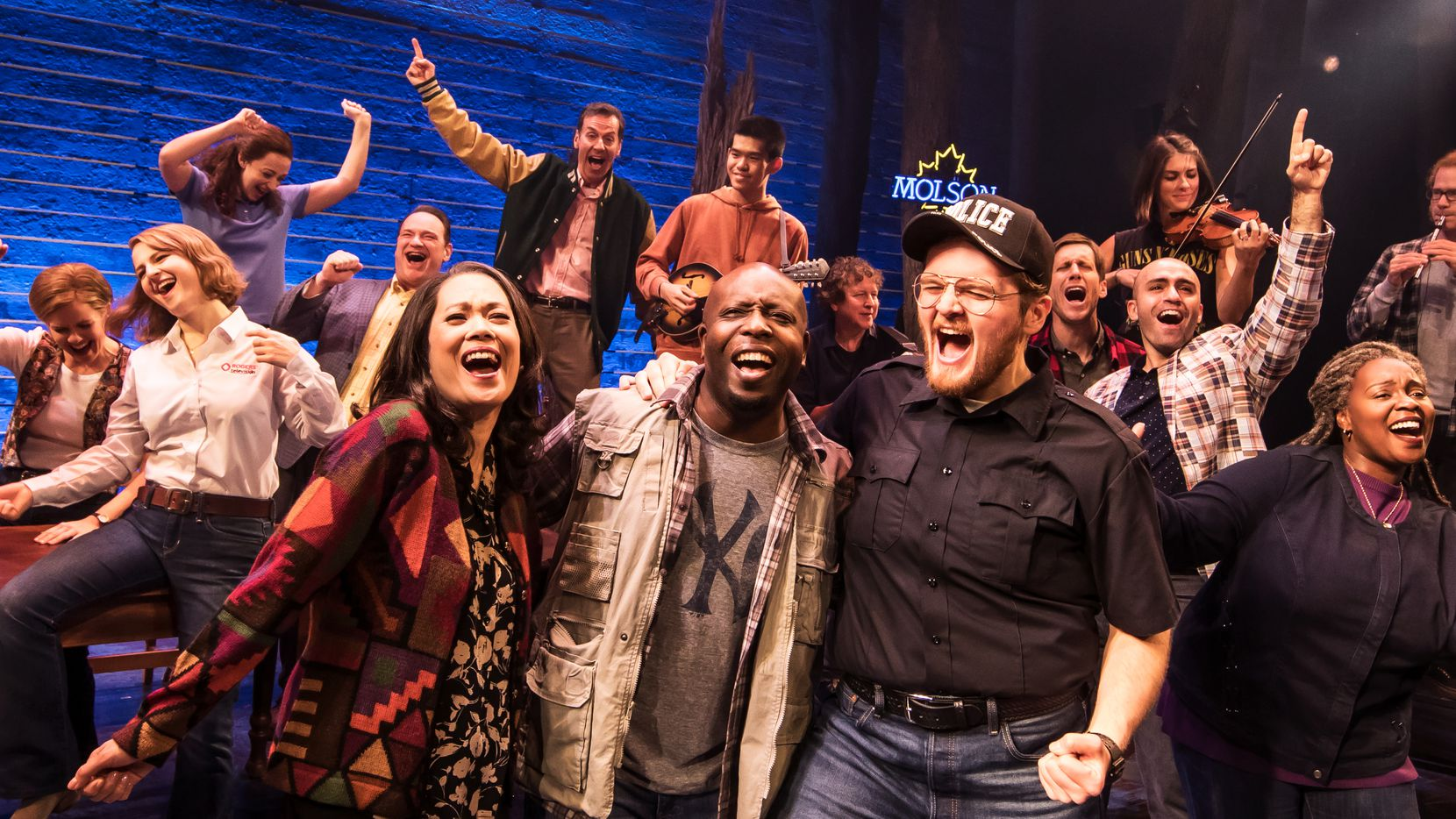 """Come From Away"" tells the story of 6,500 passengers whose planes were diverted to the small Canadian town of Gander, Newfoundland on 9/11, and the local people who took care of them for five anxious days. The North American tour of the hit Broadway musical stops in Dallas at the Music Hall at Fair Park from March 10-22. Dallas actor Chamblee Ferguson (wearing a letter jacket and pointing to the sky in background) is one of the show's 12 lead singers."
