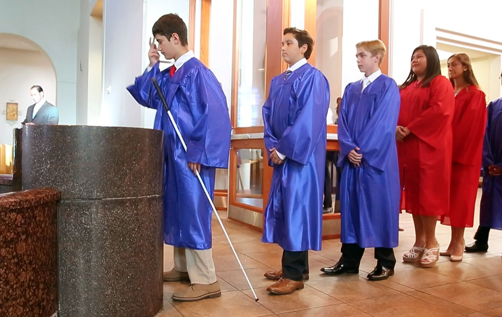 Zach makes the sign of the cross after taking holy water as he enters Mary Immaculate Catholic Church for his eighth-grade graduation.