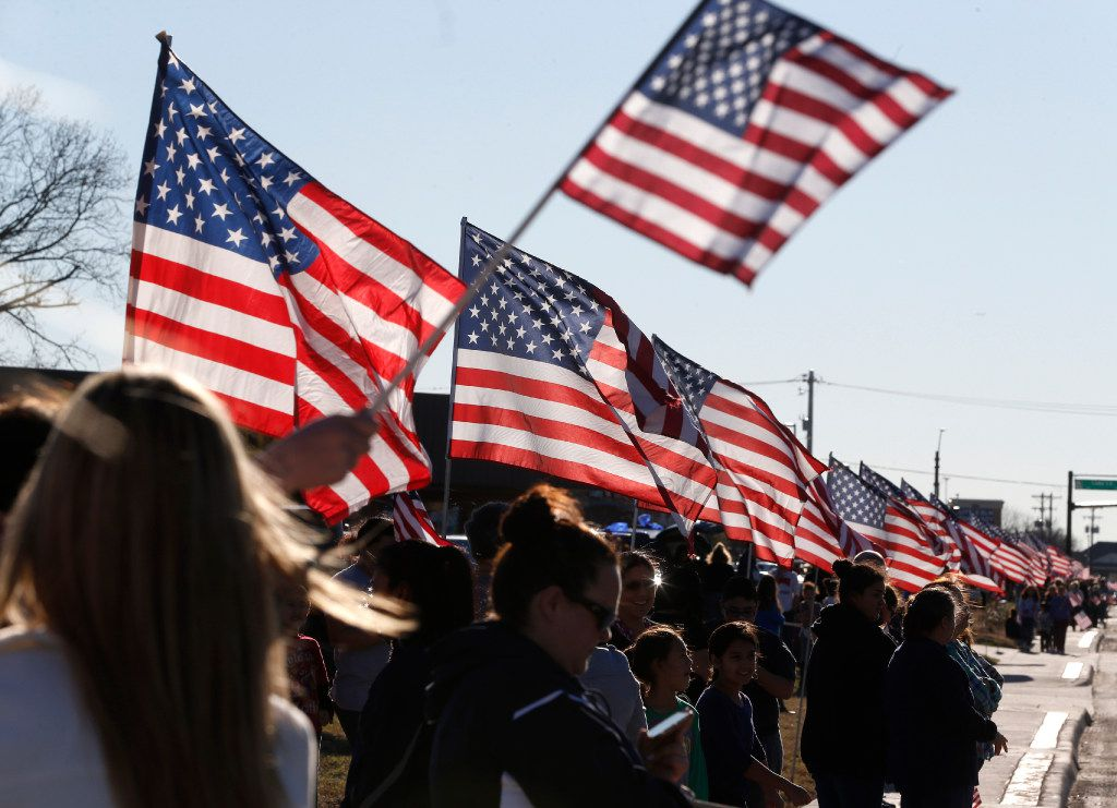 People wait with American flags line Eldorado Pkwy before the procession route for Det. Jerry Walker who was killed in the line of duty in Little Elm, Texas on January 23, 2017. (Nathan Hunsinger/The Dallas Morning News)