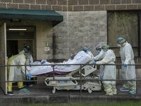 Members of the medical staff move a bed to transfer a patient to another room outside of the COVID-19 intensive care unit at the United Memorial Medical Center on July 2, 2020 in Houston, Texas. COVID-19 cases and hospitalizations have spiked since Texas reopened, pushing intensive-care wards to full capacity and sparking concerns about a surge in fatalities as the virus spreads.