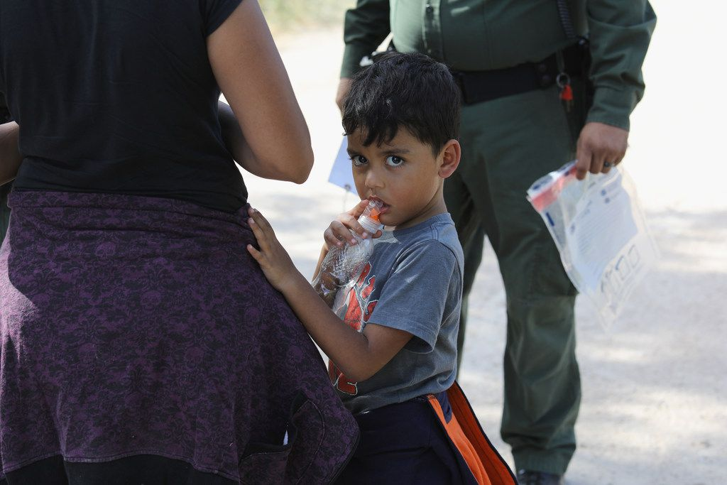 """Central American asylum seekers wait as Border Patrol agents take them into custody on June 12, 2018 near McAllen, Texas. The families were then sent to a Customs and Border Protection processing center for possible separation. U.S. border authorities are executing the Trump administration's """"zero tolerance"""" policy toward unauthorized immigrants. Attorney General Jeff Sessions also said that domestic and gang violence in immigrants' country of origin would no longer qualify them for political asylum status."""